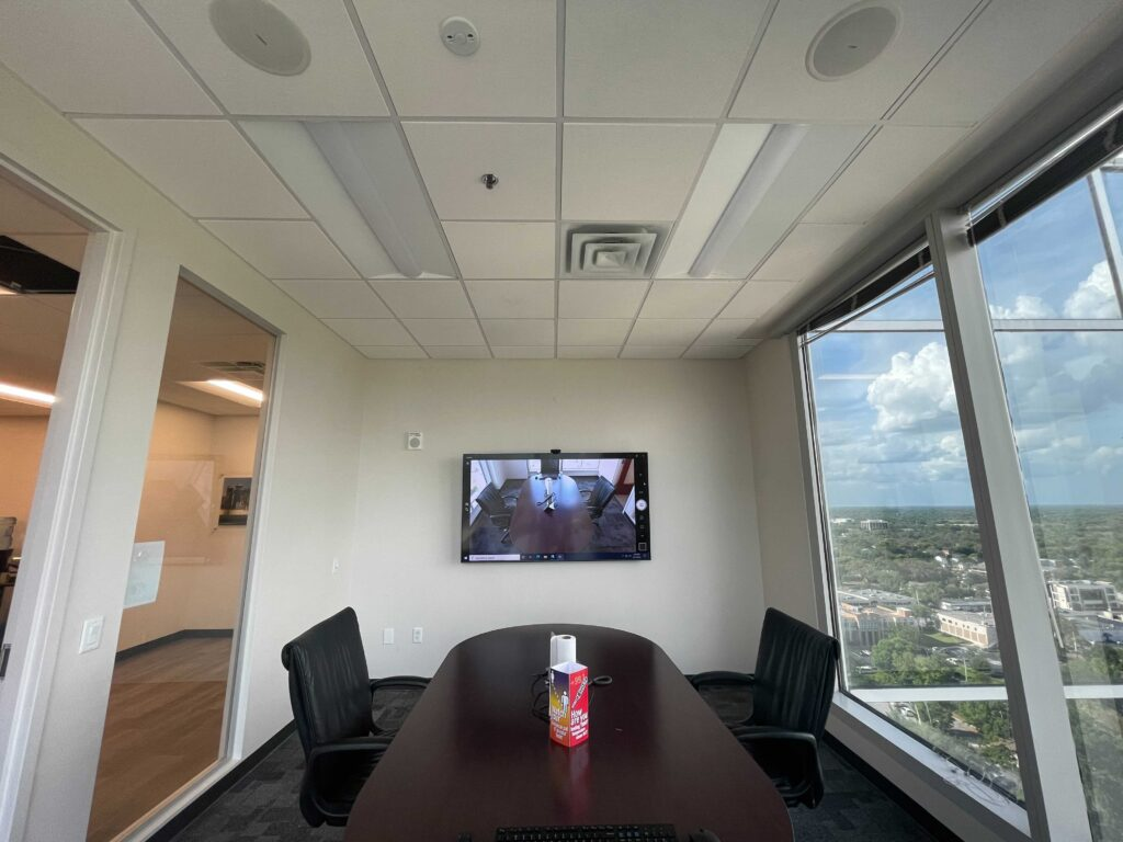 conference table facing a tv with view of skyline out the window
